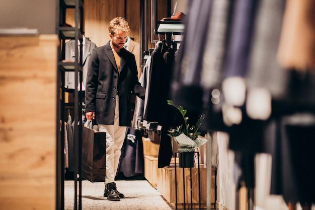 Joven de compras en la tienda de ropa masculina