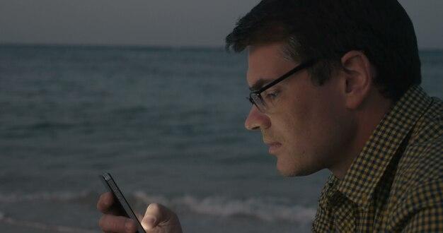 Joven comunicándose por celular junto al mar