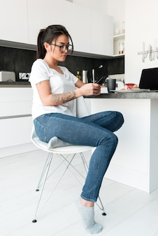 Joven concentrada sentada en la cocina