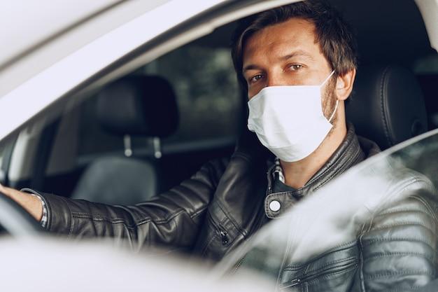 Joven conduciendo coche en máscara médica
