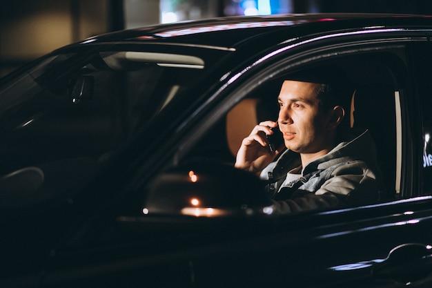 Joven conduciendo su automóvil por la noche y hablando por teléfono