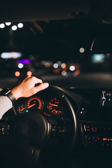 Joven conduciendo su automóvil por la noche