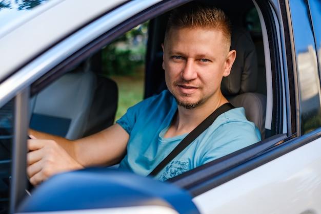 Joven conductor atractivo en coche blanco
