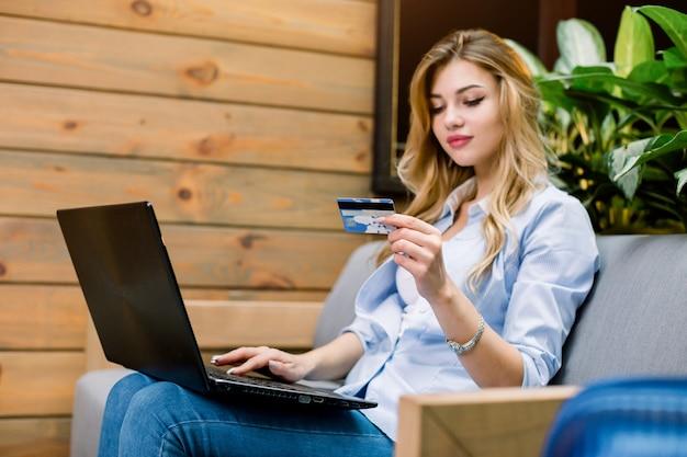 Joven confía en bastante mujer caucásica que trabaja con ordenador portátil y tarjeta de crédito, sentado en el sofá