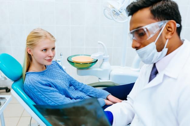 Joven confía en dentista masculino asiático control de los dientes de rayos x del paciente. concepto de clínica dental.