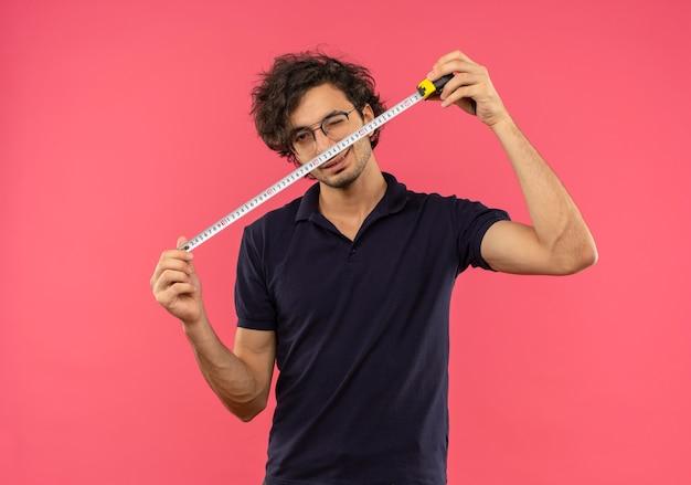 Joven confiado en camisa negra con gafas ópticas parpadea y sostiene una cinta métrica aislada en la pared rosa