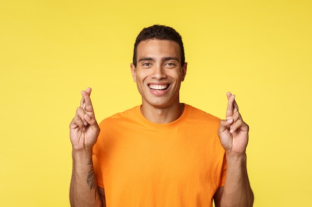 Joven confiado, esperanzado y decidido con camiseta naranja, cruzando los dedos