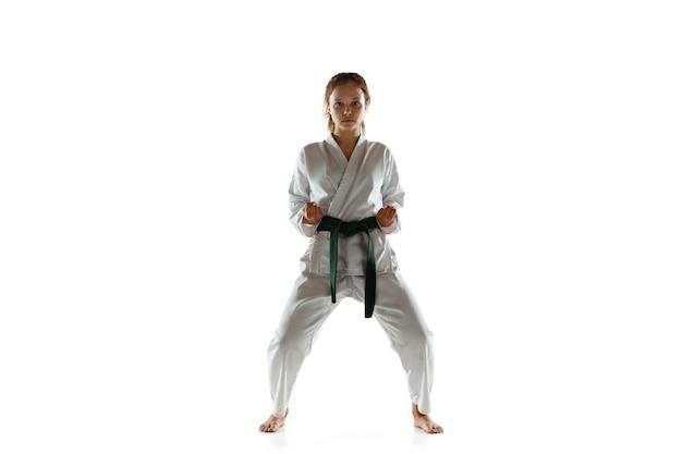Joven confiado en kimono practicando combate cuerpo a cuerpo