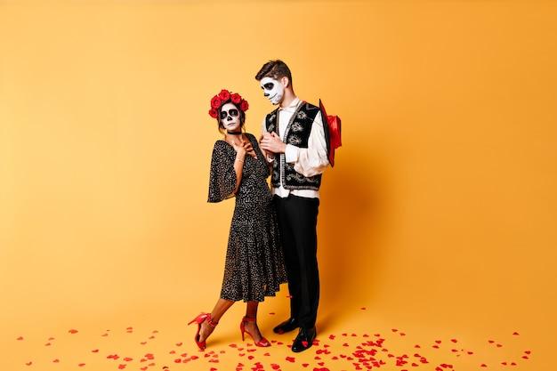 El joven confiesa a la chica enamorada sorprendida. foto de cuerpo entero de la joven pareja hermosa con la cara pintada para halloween