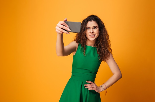 Joven confundida hacer selfie por teléfono móvil.