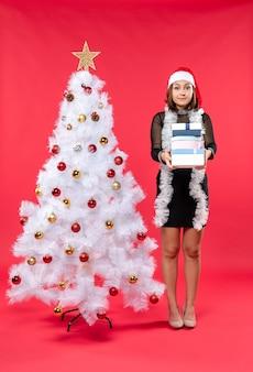 Joven confundida hermosa mujer con sombrero de santa claus y de pie cerca del árbol de navidad decorado con regalos