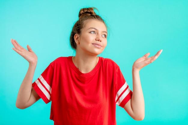 Joven confundida en moda camiseta roja con brazos encoge de hombros