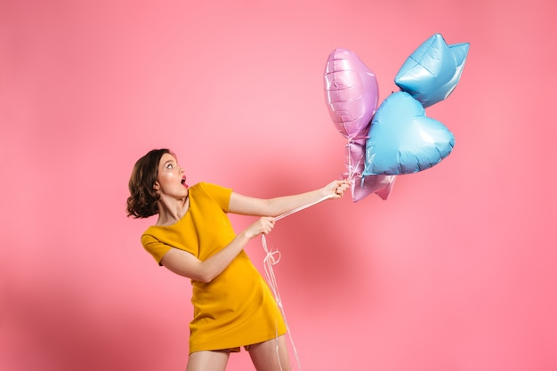 Joven confundida en vestido amarillo con globos