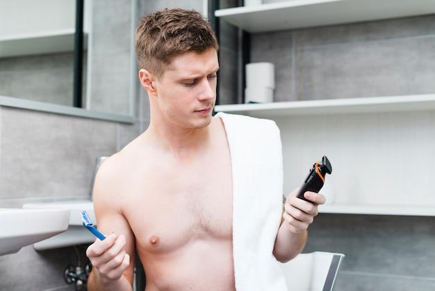 Joven confundido mirando una navaja de afeitar y recortadora en el baño