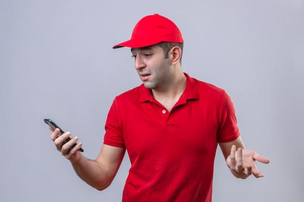 Joven confundido repartidor en polo rojo y gorra mirando la pantalla oh su teléfono inteligente decepcionado con algo de pie sobre la pared blanca aislada
