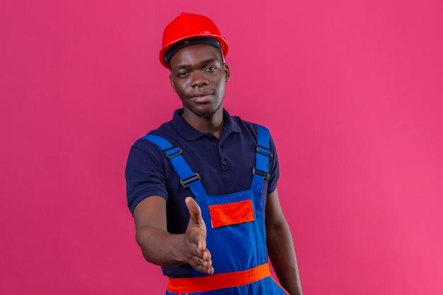 Joven constructor afroamericano hombre vestido con uniforme de construcción y casco de seguridad