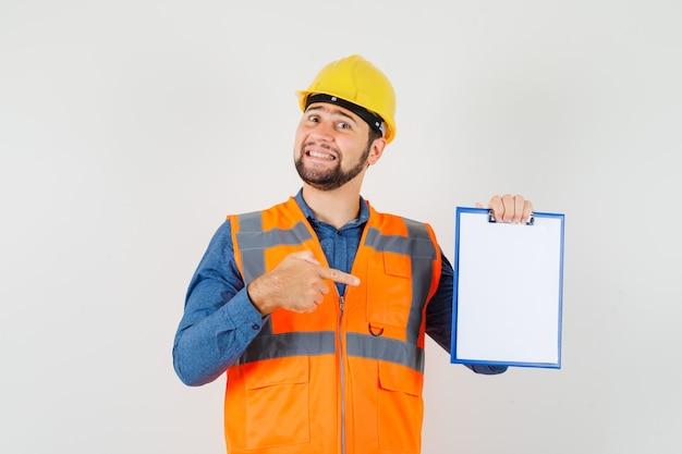 Joven constructor en camisa, chaleco, casco apuntando al portapapeles y mirando alegre, vista frontal.