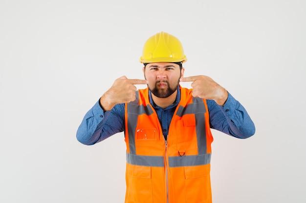 Joven constructor en camisa, chaleco, casco apuntando a su nariz mientras frunce el ceño, vista frontal.