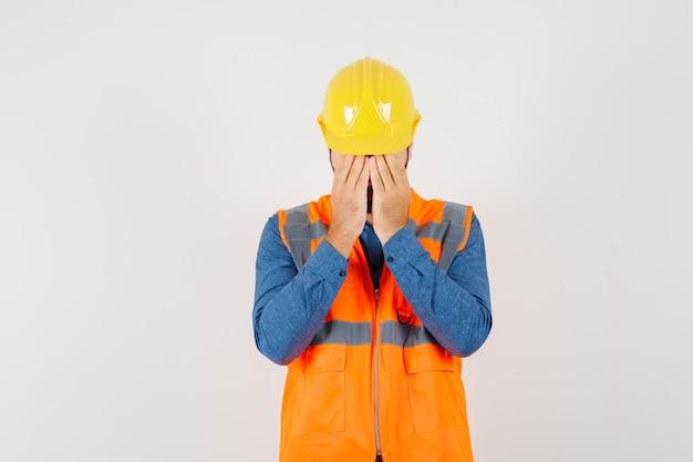 Joven constructor en camisa, chaleco, casco cubriendo la cara con las manos y mirando molesto, vista frontal.