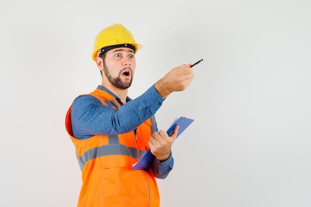 Joven constructor en camisa, chaleco, casco dando instrucciones mientras sostiene el portapapeles, vista frontal.