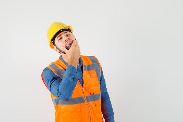 Joven constructor en camisa, chaleco, casco examinando la piel de la cara tocando su barba y luciendo guapo, vista frontal.