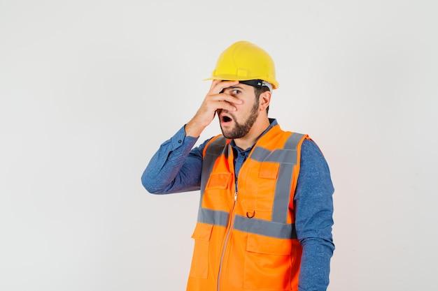 Joven constructor en camisa, chaleco, casco mirando a través de los dedos y mirando maravillado, vista frontal.