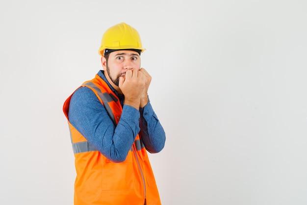 Joven constructor en camisa, chaleco, casco mordiendo los puños emocionalmente y mirando asustado, vista frontal.