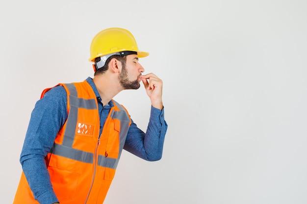 Joven constructor en camisa, chaleco, casco mostrando delicioso gesto besando los dedos y mirando encantado.
