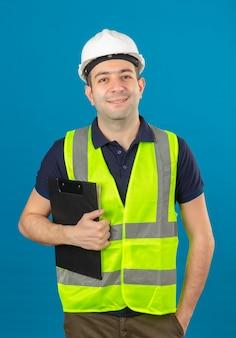 Joven constructor con casco blanco y un chaleco amarillo, sosteniendo el portapapeles con una sonrisa de pie en azul aislado