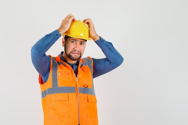 Joven constructor cogidos de la mano en la cabeza en camisa, chaleco, casco y mirando indefenso, vista frontal.