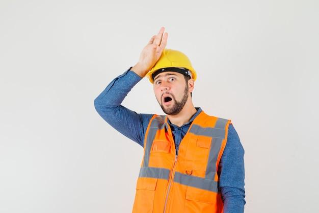 Joven constructor de la mano en la cabeza en camisa, chaleco, casco y mirando nostálgico, vista frontal.