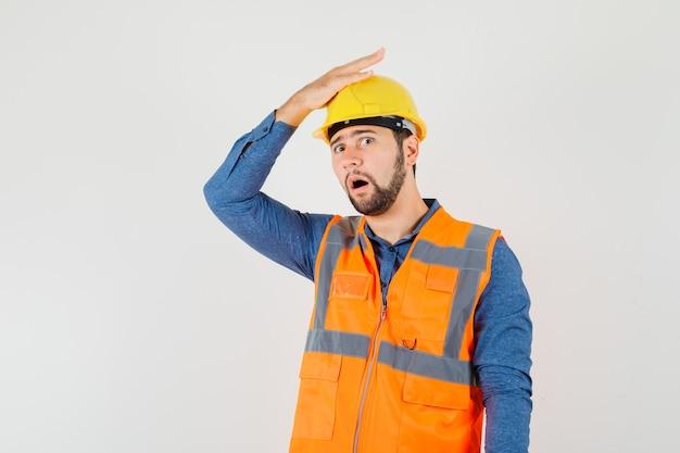 Joven constructor con la mano en la cabeza en camisa