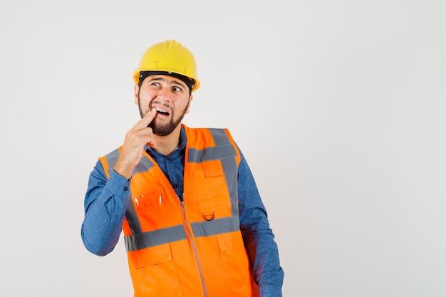 Joven constructor que sufre de dolor de muelas en camisa, chaleco, casco y parece incómodo. vista frontal.