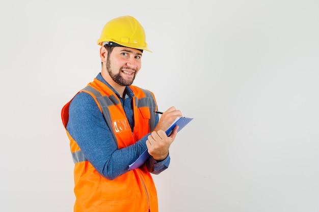 Joven constructor tomando notas en el portapapeles en camisa, chaleco, casco y luciendo alegre. vista frontal.