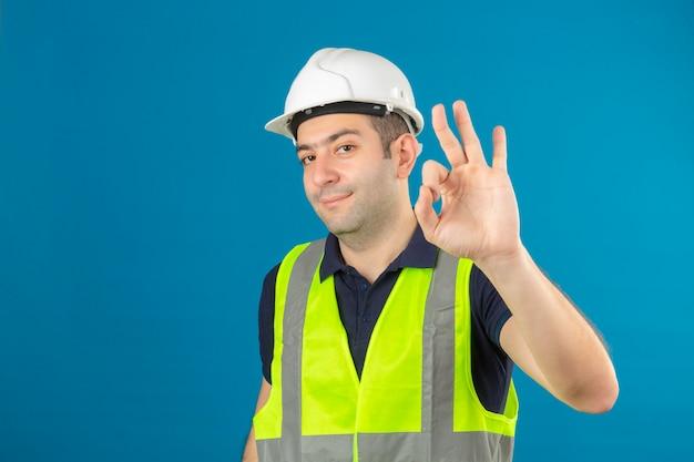 Joven constructor con uniforme de construcción y casco de seguridad en azul aislado sonriendo positivo haciendo aceptar firmar con la mano y los dedos
