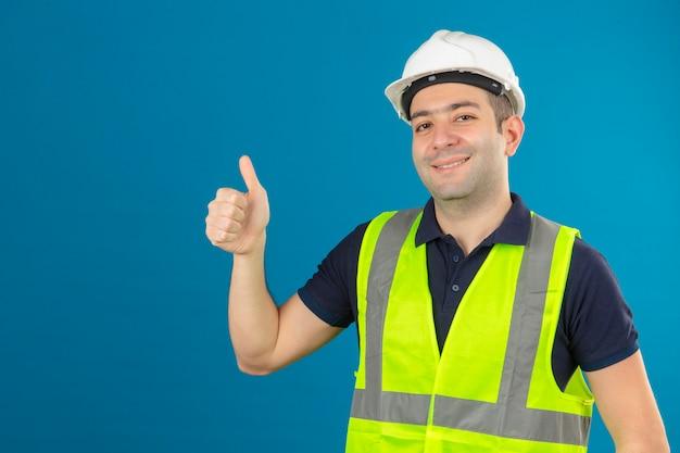 Joven constructor con uniforme de construcción y casco de seguridad en azul aislado sonriendo positivo haciendo feliz pulgares arriba gesto con la mano