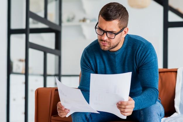 Joven, consultar documentos en casa
