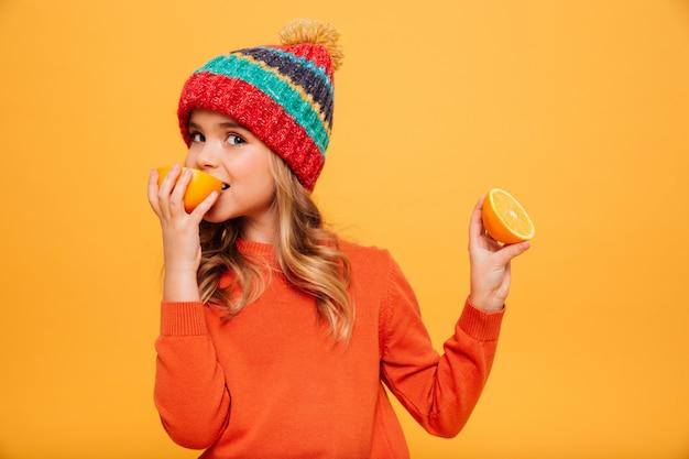 Joven contenta en suéter y sombrero comiendo naranja mientras mira a la cámara sobre naranja