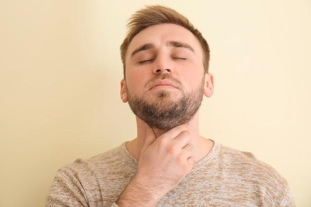 Joven control de la glándula tiroides sobre fondo de color