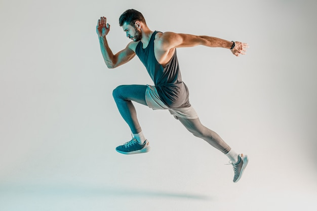 Joven corredor europeo concentrado barbudo. vista lateral del deportista con uniforme deportivo. aislado sobre fondo turquesa. sesión de estudio. copia espacio