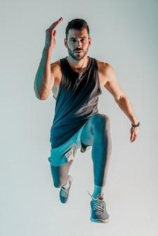 Joven corredor europeo serio barbudo saltando. vista frontal del deportista con uniforme deportivo y mirando a la cámara. aislado sobre fondo gris con luz azul. sesión de estudio