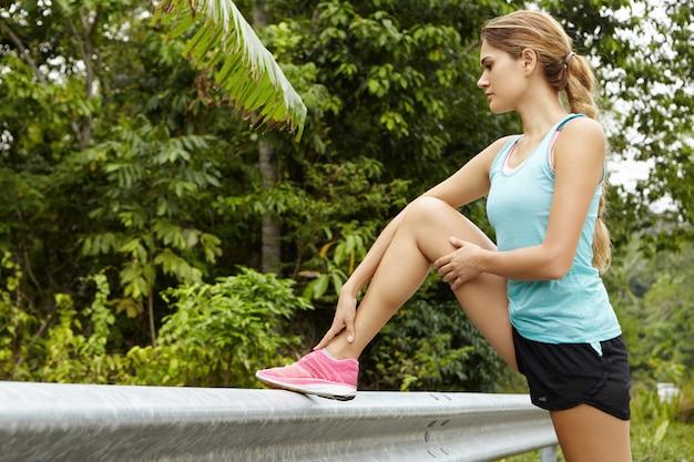 Joven corredor de mujer caucásica en zapatillas rosa calentando antes del maratón, de pie en la carretera, colocando su pierna en la barandilla.