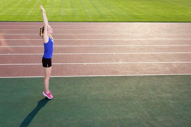 Joven corredor que se extiende antes de correr en la pista del estadio