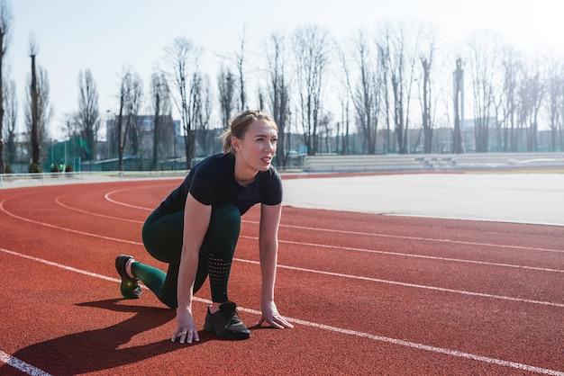 Joven corredor en ropa deportiva se prepara para el sprint en la línea de salida en la pista del estadio revestido de rojo en un día soleado