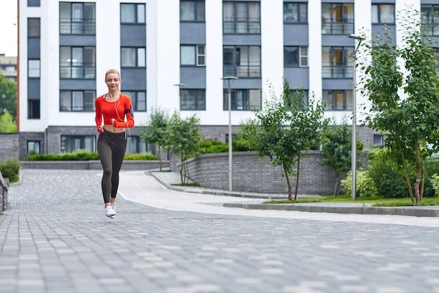 Joven corredora con capucha está corriendo en la calle de la ciudad