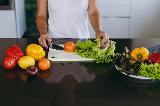 La joven corta verduras en la cocina con un cuchillo