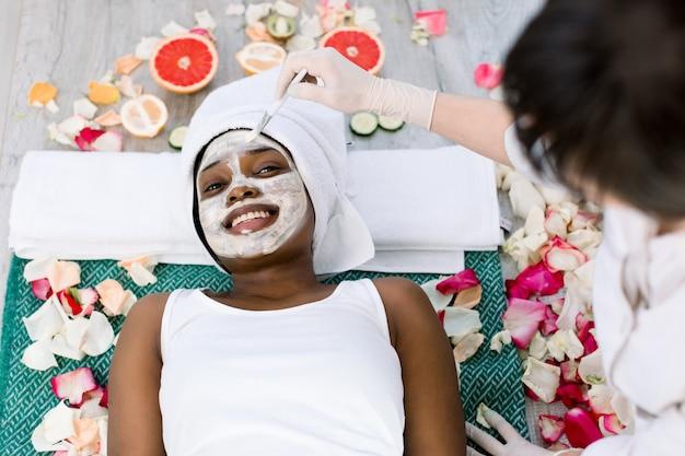 Joven cosmetóloga caucásica aplicar máscara cosmética en la cara de la mujer africana en un salón de belleza. mujer con máscara en la cara relajante en un salón de belleza