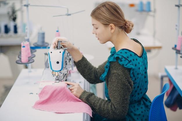 Joven costurera hermosa cose en la máquina de coser en fábrica de telas