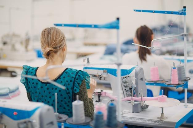 Joven costurera hermosa cose en la máquina de coser en fábrica