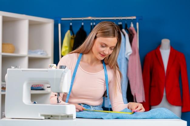 Joven costurera trabajando en su máquina de coser en fábrica textil